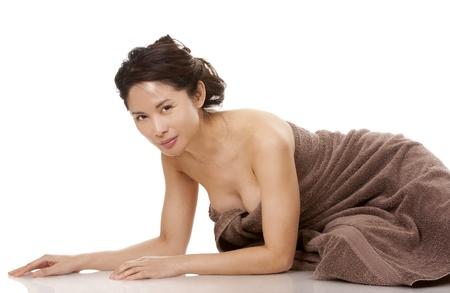 mujer desnuda sentada: bella asiática morena llevaba una toalla marrón sobre fondo blanco