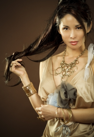 beautiful asian brunette wearing jewellery and fashin dress on dark background photo