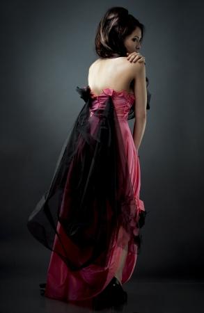 beautiful asian brunette wearing jewellery and fashin dress on dark background photo