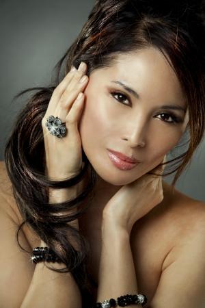 beautiful asian brunette wearing jewellery and fashin dress on dark background Stock Photo - 16130339