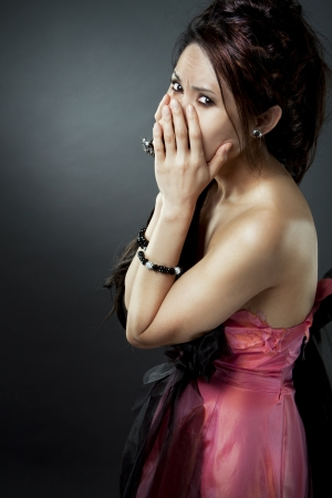 beautiful asian brunette is covering her face with hands photo