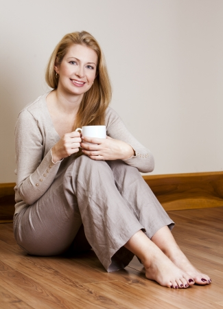 pretty blond woman wearing beige top relaxing on the floor Stock Photo - 16302400