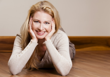 pretty blond woman wearing beige top relaxing on the floor Stock Photo - 16302398