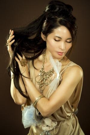 beautiful asian brunette wearing jewellery and fashin dress on dark background Stock Photo - 16302395