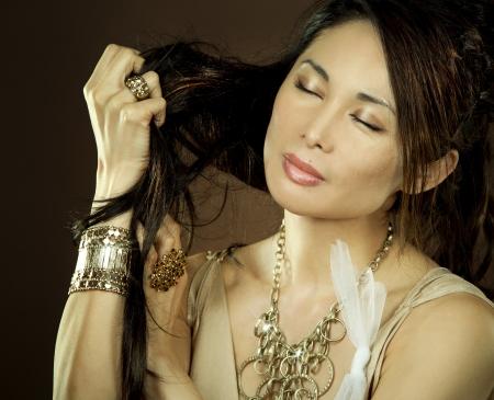 beautiful asian brunette wearing jewellery and fashin dress on dark background Stock Photo - 16302390