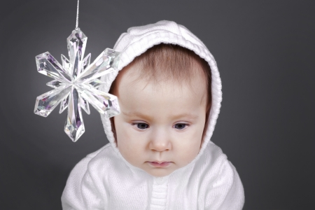 beautiful baby girl is sitting sad with snow flake ornament Stock Photo - 16302358
