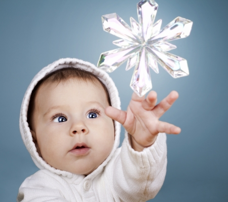 beautiful baby girl is playing with snow flake ornament Stock Photo - 16302351