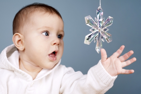 beautiful baby girl is playing with snow flake ornament Stock Photo - 16302355