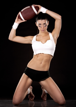 american sexy girl: athletic brunette posing as american football girl on black background