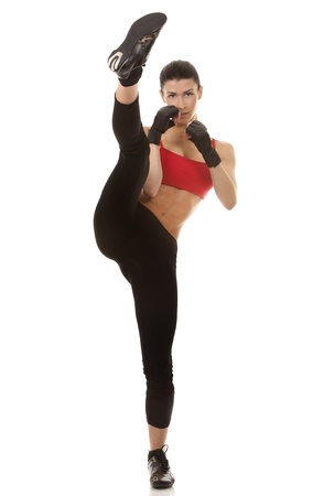 self confident: athletic brunette wearing boxing gloves on white isolated background