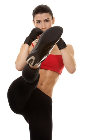 kick boxer: athletic brunette wearing boxing gloves on white isolated background
