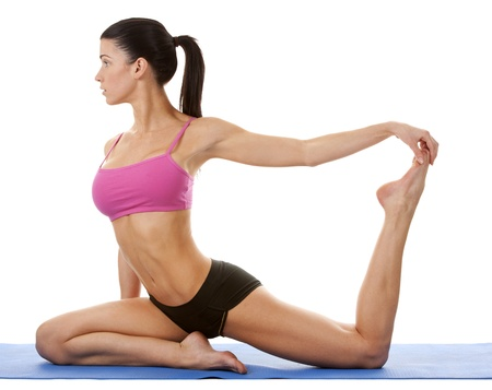 active brunette in yoga position on white isolated background photo