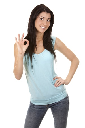 casual brunette showing ok gesture on white background Stock Photo - 16560075