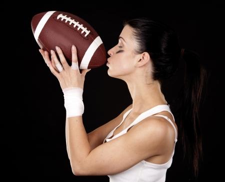 athletic brunette posing as american football girl on black background Stock Photo - 16560076