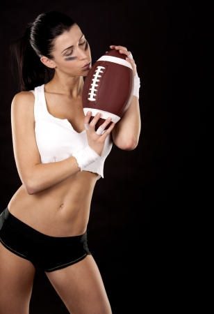 athletic brunette posing as american football girl on black background Stock Photo - 16560077