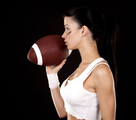 athletic brunette posing as american football girl on black background Stock Photo - 16560078