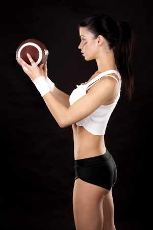 athletic brunette posing as american football girl on black background Stock Photo - 16560084