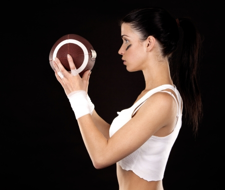 athletic brunette posing as american football girl on black background Stock Photo - 16560073