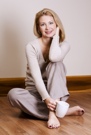 pretty blond woman wearing beige top relaxing on the floor Stock Photo - 16607692