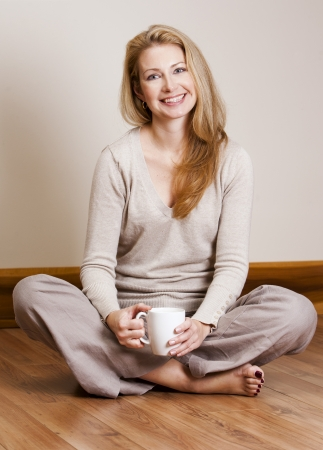 pretty blond woman wearing beige top relaxing on the floor Stock Photo