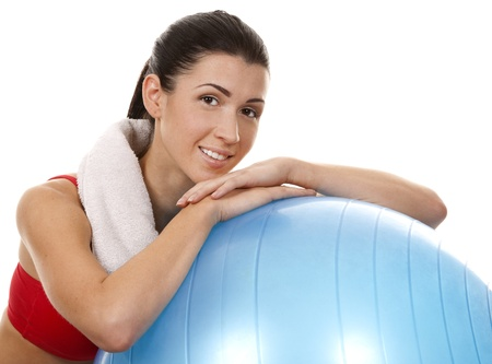 active brunette in red posing with exercise ball on white background Stock Photo - 16656747