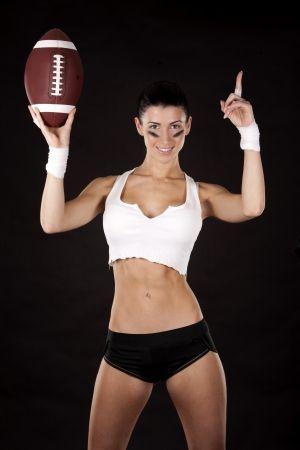 athletic brunette posing as american football girl on black background Stock Photo - 16656797