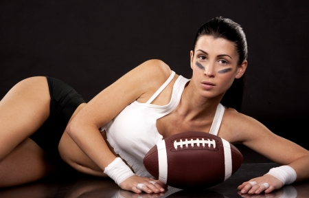 athletic brunette posing as american football girl on black background photo