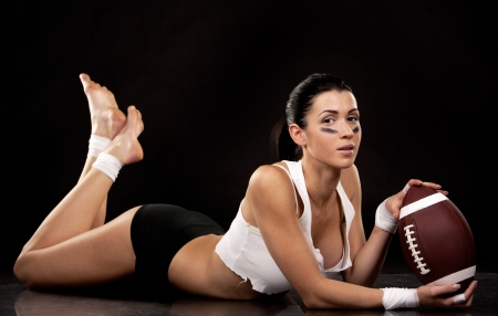 youth football: athletic brunette posing as american football girl on black background