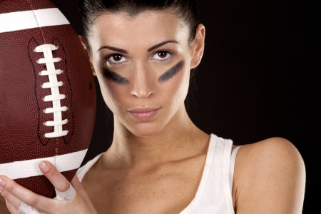 attitude girls: athletic brunette posing as american football girl on black background