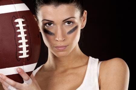 football play: bruna atletico in posa come ragazza football americano su sfondo nero