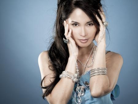beautiful asian brunette wearing jewellery and fashin dress on blue background