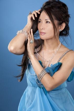 beautiful asian brunette wearing jewellery and fashin dress on blue background Stock Photo - 16757026