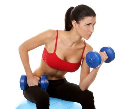 female muscle: athletic brunette lifting weights on white isolated background
