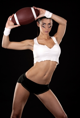 athletic brunette posing as american football girl on black background Stock Photo - 16878871