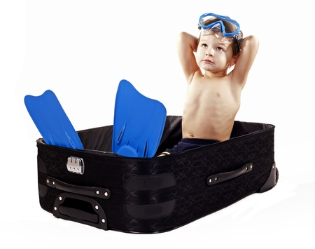 little boy sitting in the luggage wearing snorkel gear photo