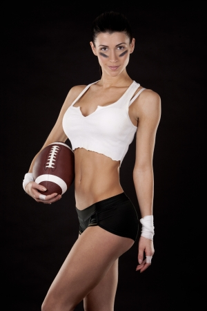 athletic brunette posing as american football girl on black background Stock Photo - 17573599