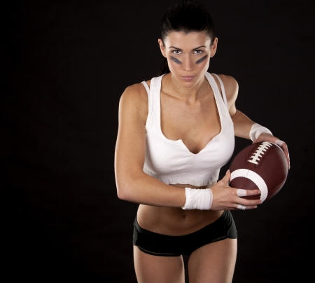 athletic brunette posing as american football girl on black background Stock Photo - 17602576