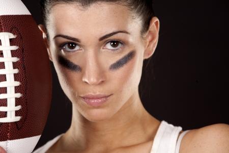 athletic brunette posing as american football girl on black background