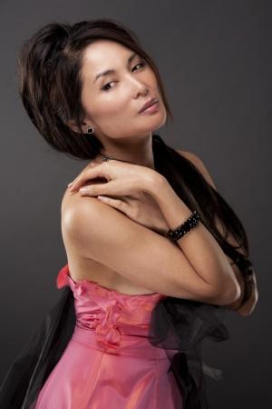 beautiful asian brunette wearing jewellery and fashin dress on dark background Stock Photo - 17573627