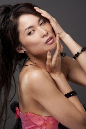 beautiful asian brunette wearing jewellery and fashin dress on dark background Stock Photo - 17573626
