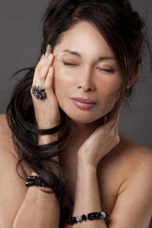beautiful asian brunette wearing jewellery on dark background Stock Photo - 17573621
