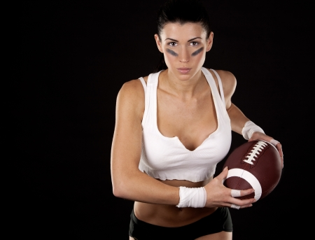 athletic brunette posing as american football girl on black background Stock Photo - 17699131