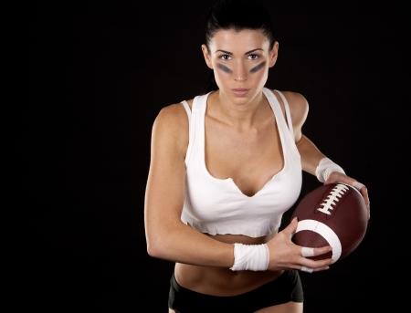 athletic brunette posing as american football girl on black background Stock Photo - 17699131
