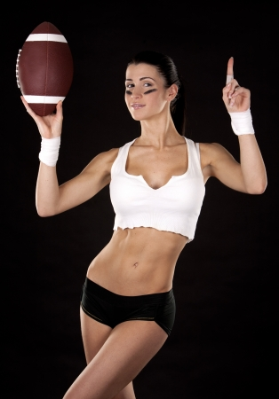 athletic brunette posing as american football girl on black background Stock Photo - 17699136