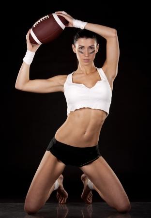 athletic brunette posing as american football girl on black background Stock Photo - 17699134