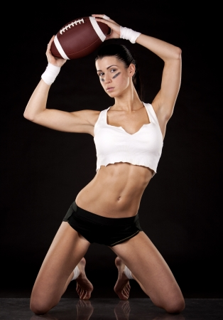 athletic brunette posing as american football girl on black background Stock Photo - 17699138