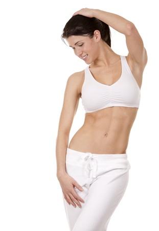 cintura perfecta: bonita morena en ropa blanca activa en el fondo blanco Foto de archivo