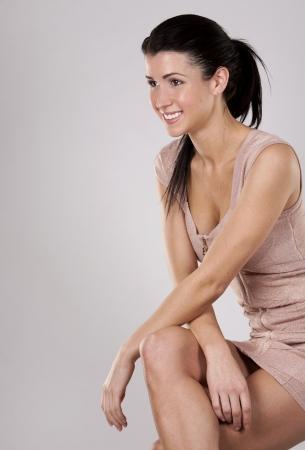 pretty brunette wearing pencil dress on light grey background photo