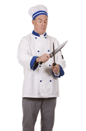 sharpening: mature chef wearing workwear on white isolated background Stock Photo