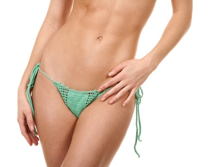 pretty fitness model posing in green bikini on white background photo